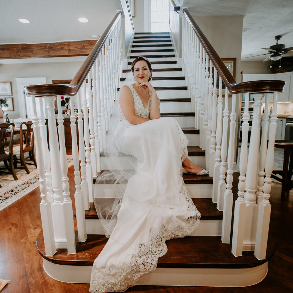 Bride sitting and smiling contently on stairway in farm house