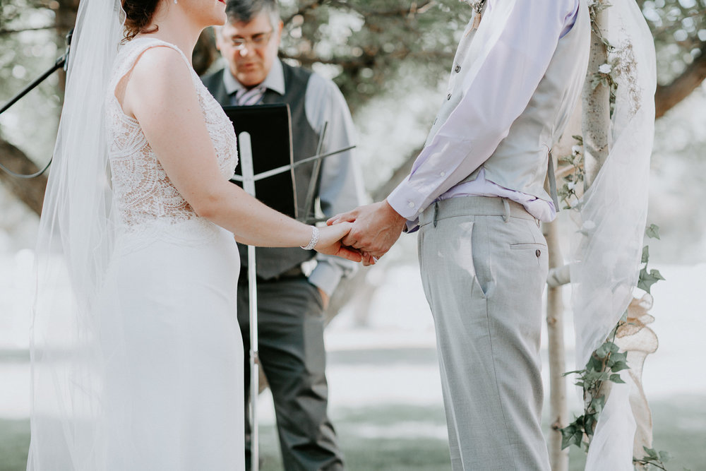Close up of bride and groom holding hands during ceremony with officiant