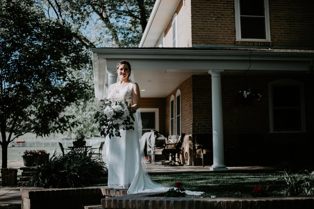 Bride standing alone in front of farmhouse porch