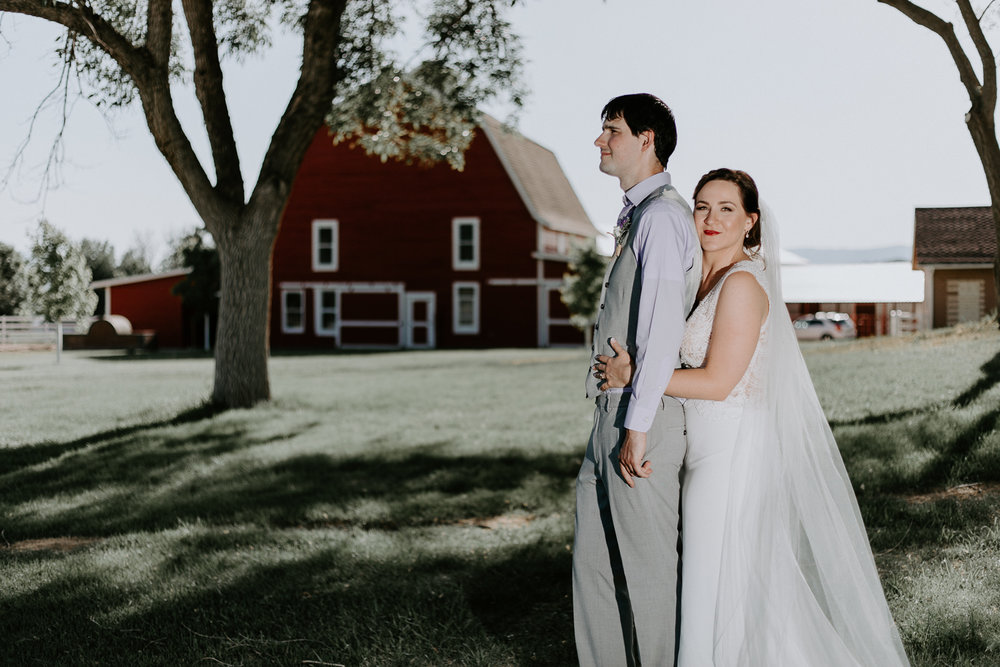 Bride holding groom from behind with barn behind them