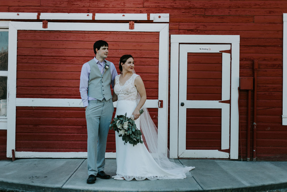 Newlyweds standing in front of red barn and looking in same direction