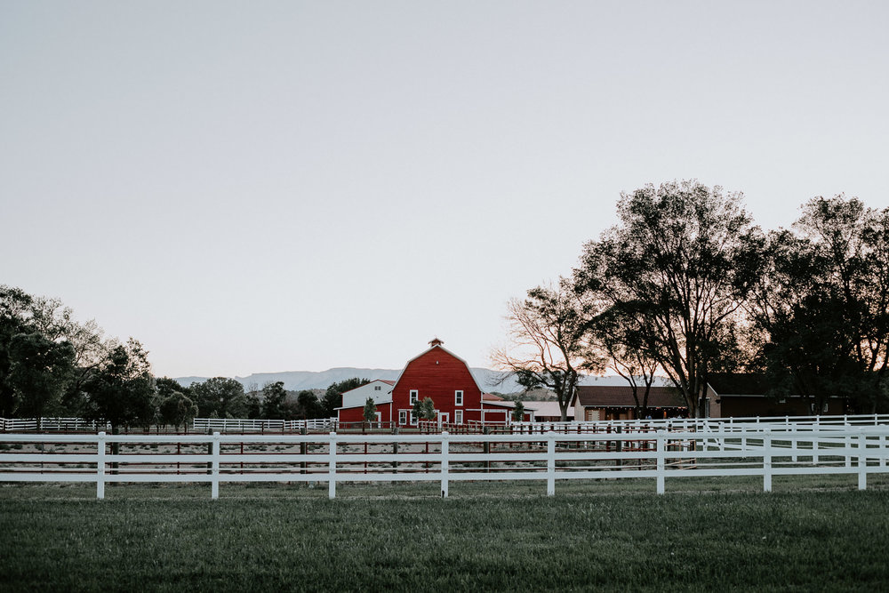 Red Barn Guest Ranch seen from afar with white fence in foreground