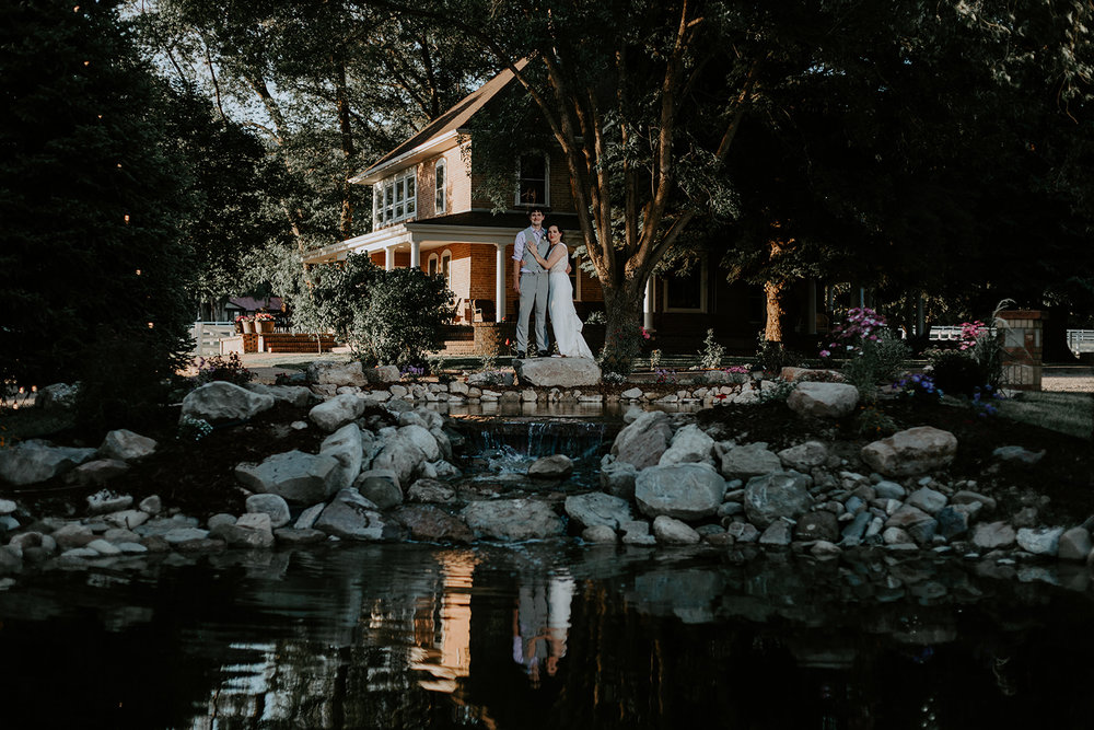 Wide angle of bride and groom behind lake with farmhouse in background