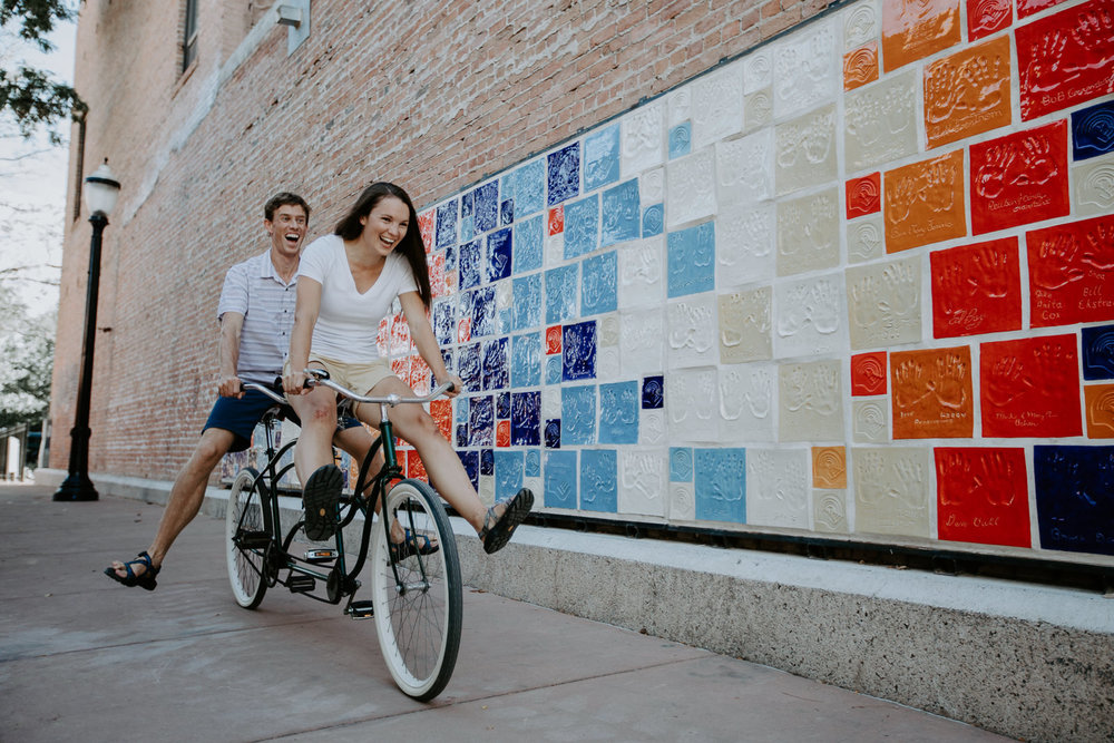 Couple riding tandem bike with legs extended giggling in colorful United Way Grand Junction alley