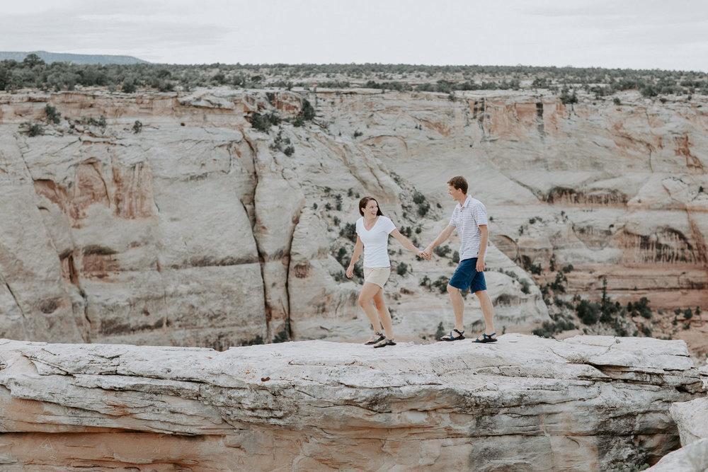 Woman leading man along rocky terrain