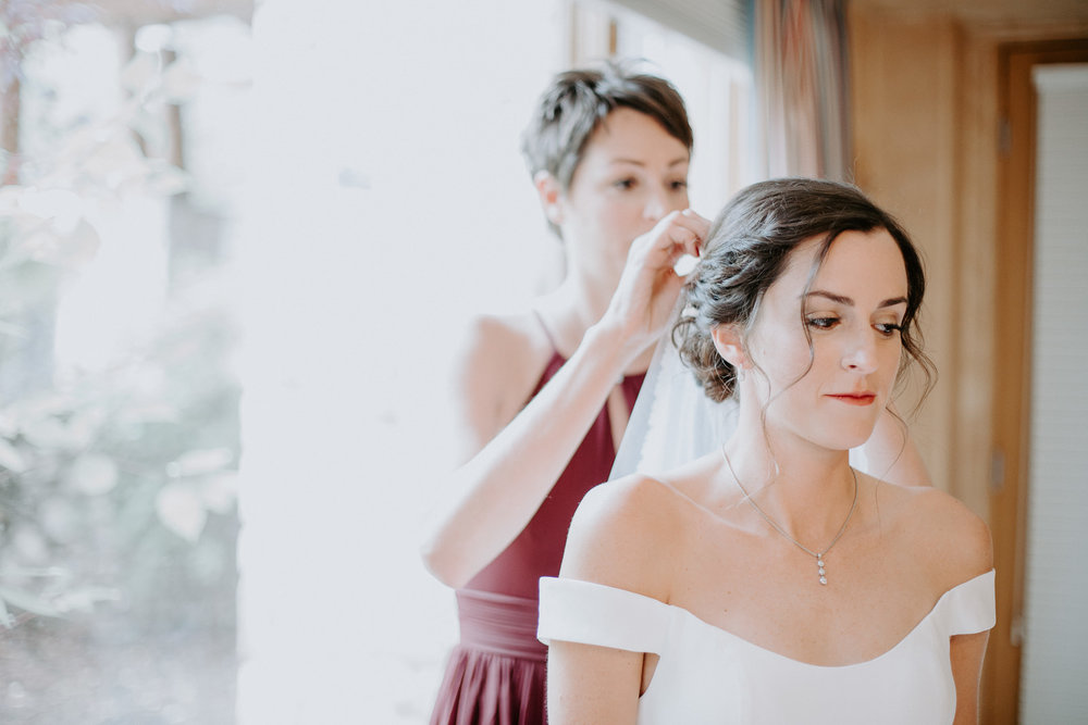 Bride's older sister helping put her hair piece in while she gets ready