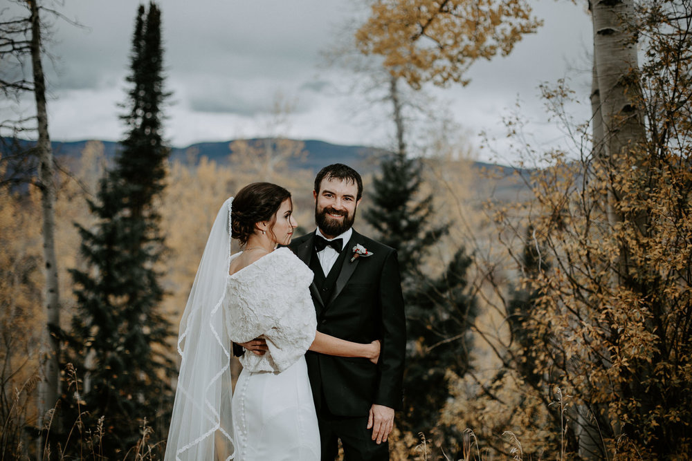 Bride looking at groom while he smiles at camera with fall colors behind them