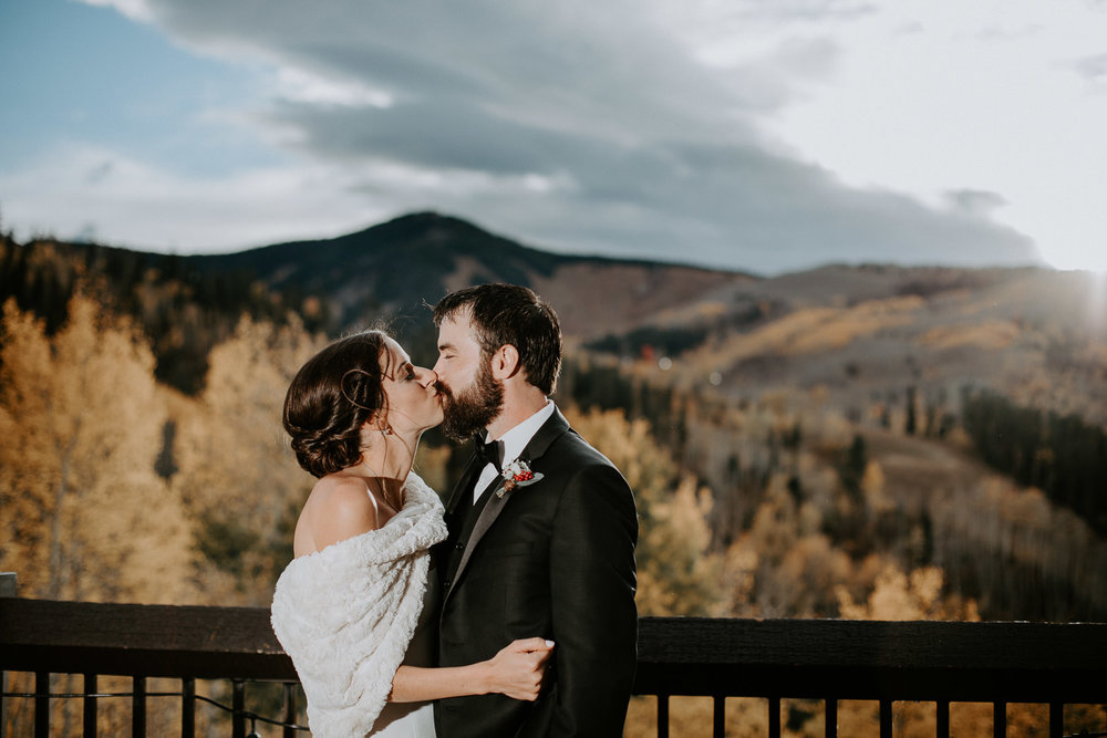 Bride and groom kissing on deck overlooking mountains and fall colors in Beaver Creek