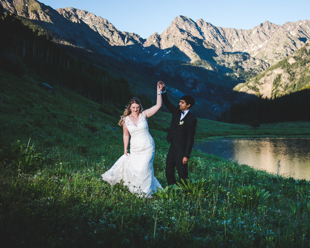 Groom spinning bride with mountains in background at Piney River Ranch north of Vail Colorado