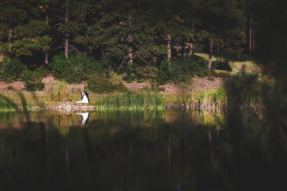 Bride and groom embracing being reflected in lake in Mancos Colorado