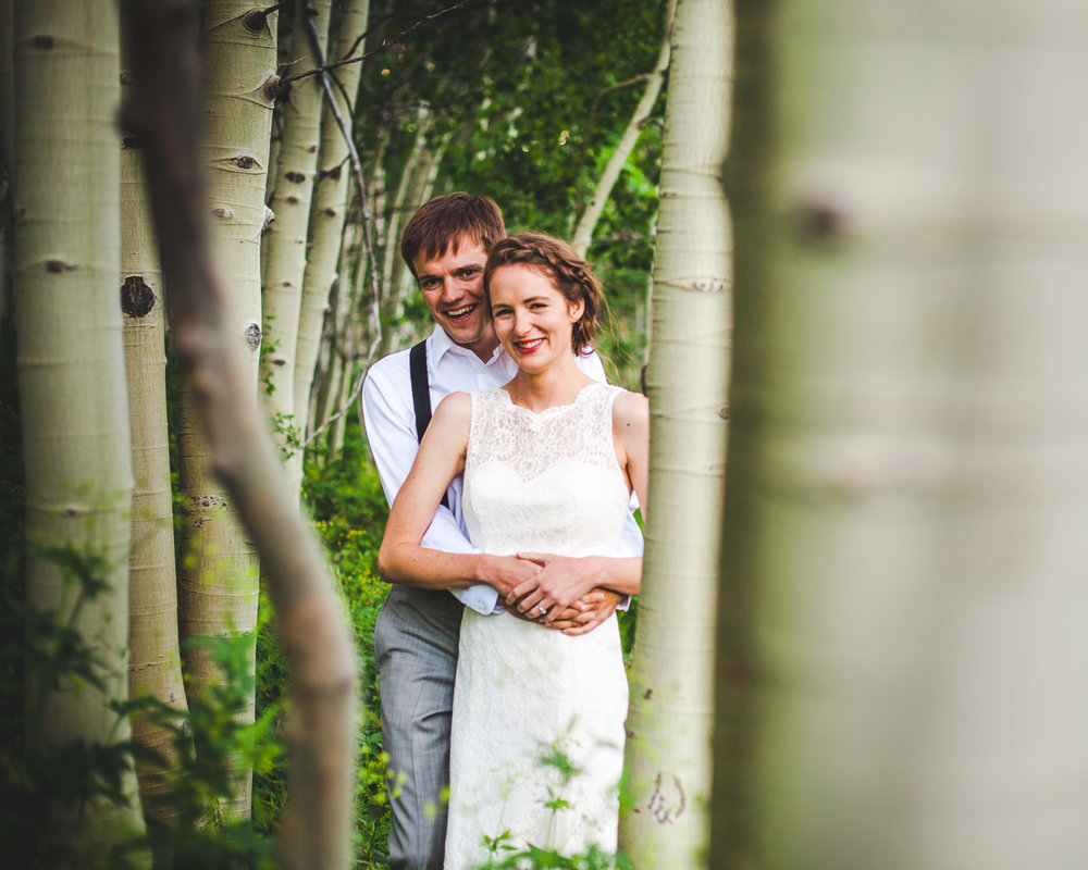 Groom and bride standing among aspens holding each other in Crested Butte