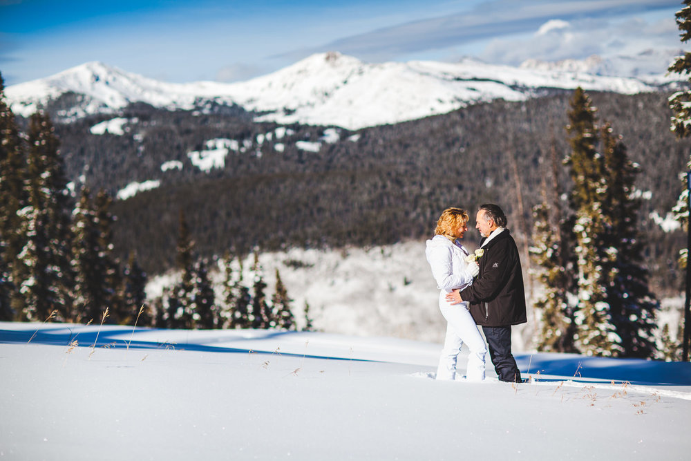 Just wed couple standing in snow looking at each other with Gore Range in background at Copper Mountain Resort