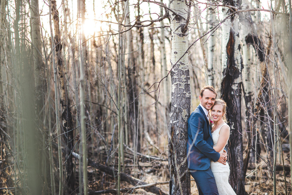 Smiling wed couple hugging among aspens with light peering through