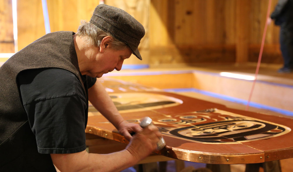 Master Carver Steve Brown forms copper to the screen for the Shakes Tribal House.