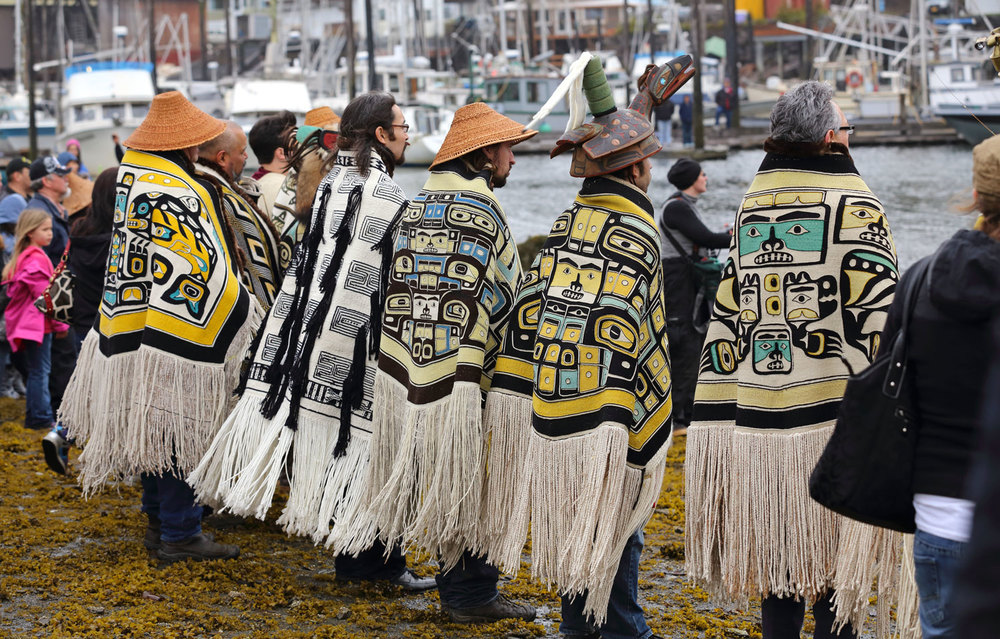 Alaska Native Elders and clan leaders wearing Chilkat and ravenstail blankets.