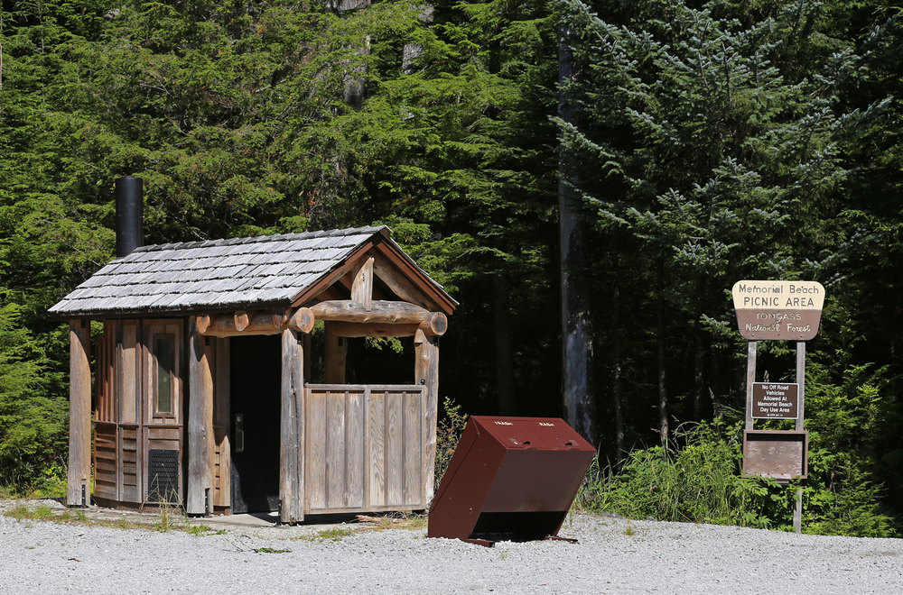 Parking lot and outhouse at Memorial Beach. In front of the outhouse are bear-proof trash cans.