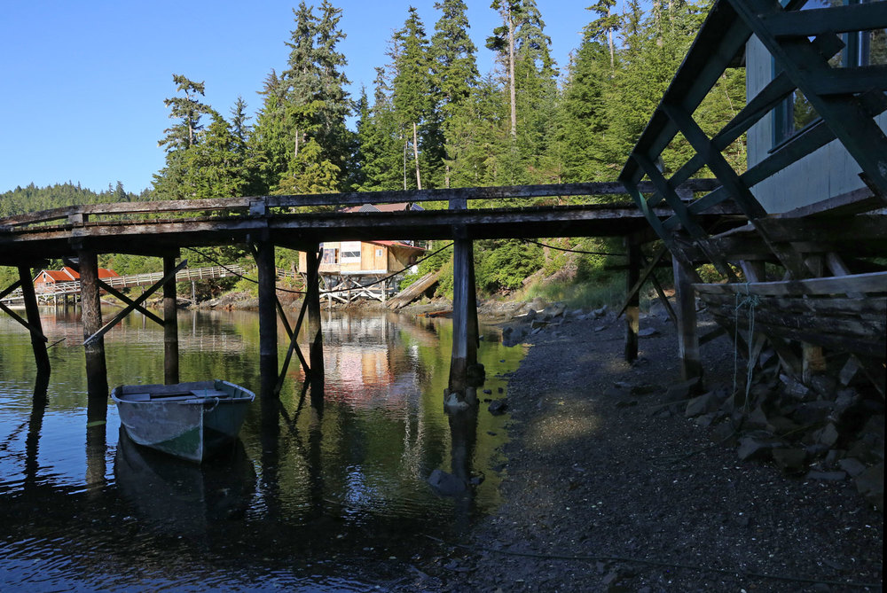 Walk under the dock in the foreground and continue along the beach to the next house.
