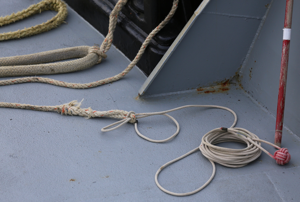 The light heaving line has a Monkey's Fist knot on one end. The other end is tied to another line, and that is tied to the heavy hawser line. The hawser secures the boat to the dock.