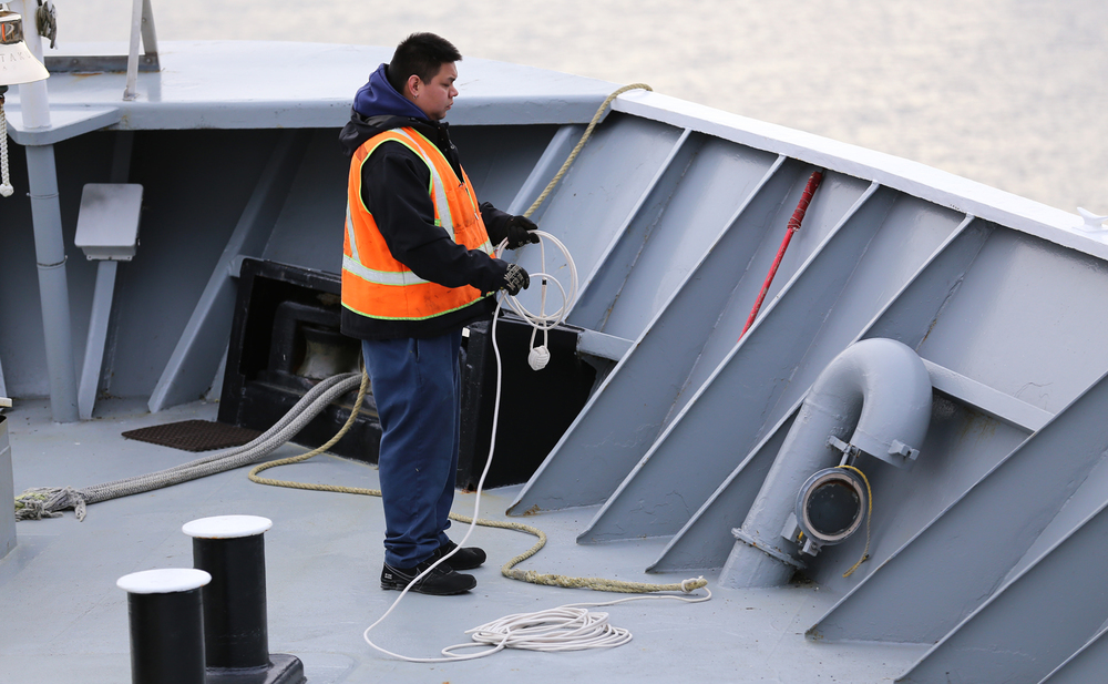 "The deckhand coiling the heaving line for a clean throw from the bow of the Alaska Marine Highway ferry ""Taku""."