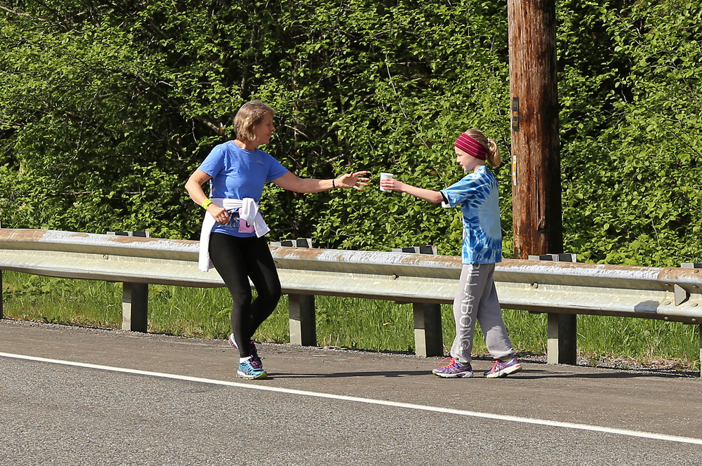 Rylee gets back to work and hands off a cup of water to a runner.