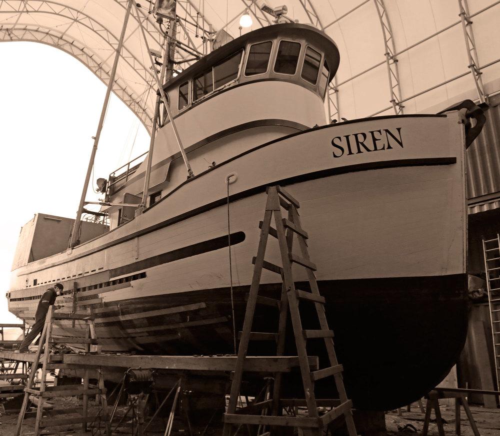 Mike File working on replacing planks replanking fishing boat FV Siren built in 1919 Petersburg Wrangell Alaska Marine Service Center boatyard shipyard
