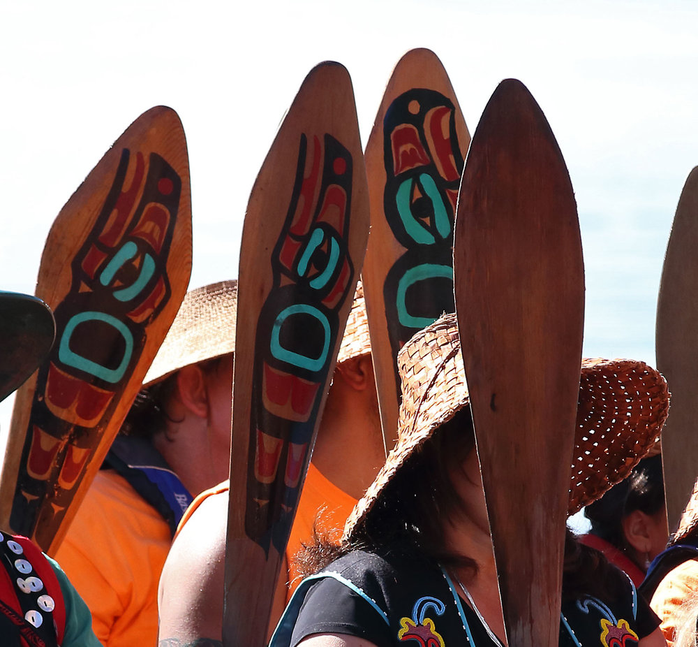 Paddles raised, the Haida people wait to go ashore.