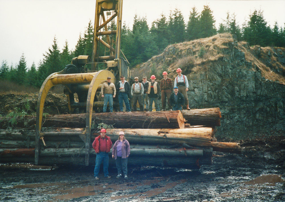 Photo courtesy of Tim and Theresa Lindseth. Back row: Stacker operator Chris Lewis, A-frame operator Eddie Nelson, Boom Man Tim Lindseth, Mike McKim, Bander Tim Lindseth Jr., Bander Wade Adamson, Bucker Joe Holland, Danny Killian. Front row: Jack Sims, Lorraine Sims.