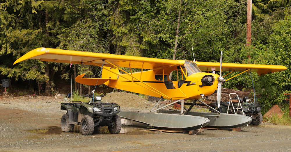Piper J3 Cub tied down to 4-wheelers ATVs quads in Southeast Alaska