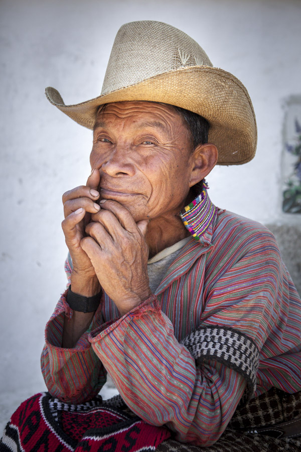 A Mayan man dressed in traditional clothing who has survived so much blood shed in the 1980's sit contemplative on the steps of a church. Engaging and photographing Mayan villagers was a major reason for working with a Guatemala NGO in 2012.