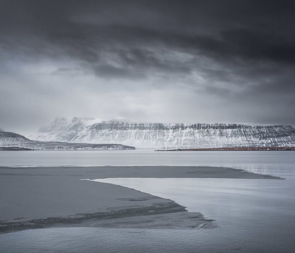 An ice sheet drifts past in the ebbing tide while storm clouds move over distant mountains.