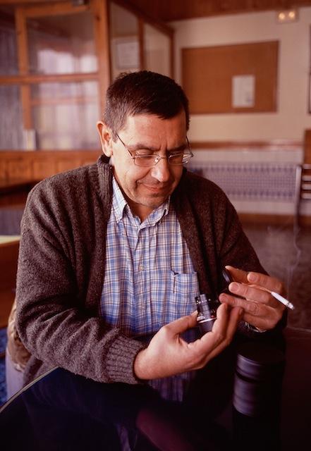 Mi amigo Paco examinando un summicron de quinta mano que compre para acompañar a mi primera leica,Inviernodel 2005 en un bar de algún pueblodel Rincón de Ademuz. © Daniel Belenguer