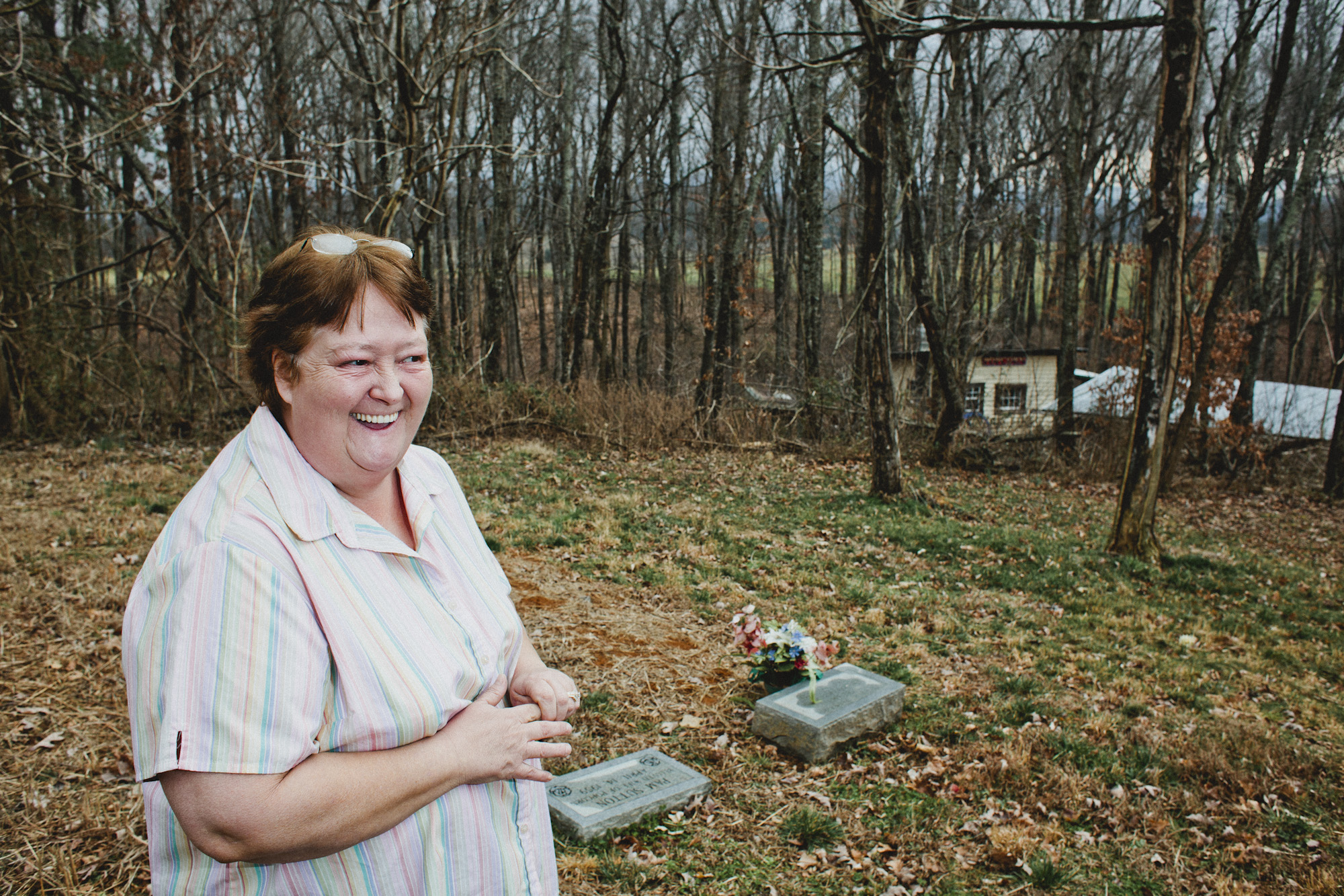 Pam Sutton stands in front of Popcorn's grave, which is up the hill where his stills once sat. The gravestone beside his is reserved for her.