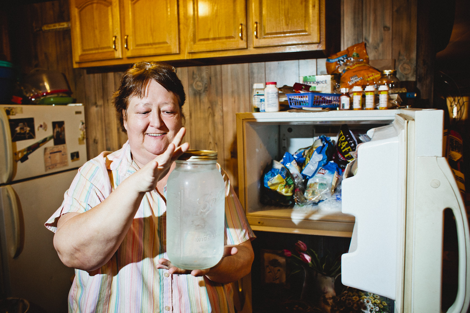 Pam Sutton, Popcorn's widow, keeps a batch of Popcorn's whiskey in the freezer. A picture of Popcorn hangs in the house.