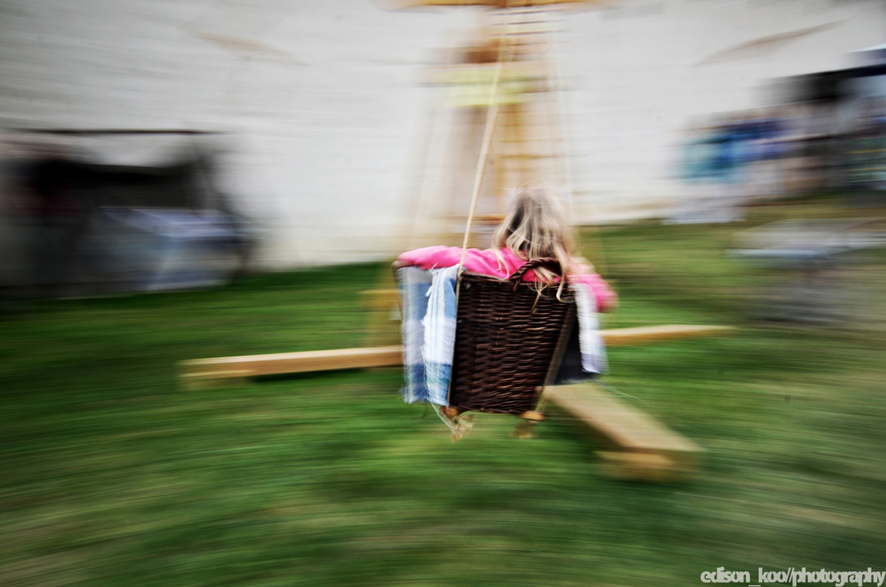 A wooden contraption to swing kids by hand in wicker baskets. So simple.