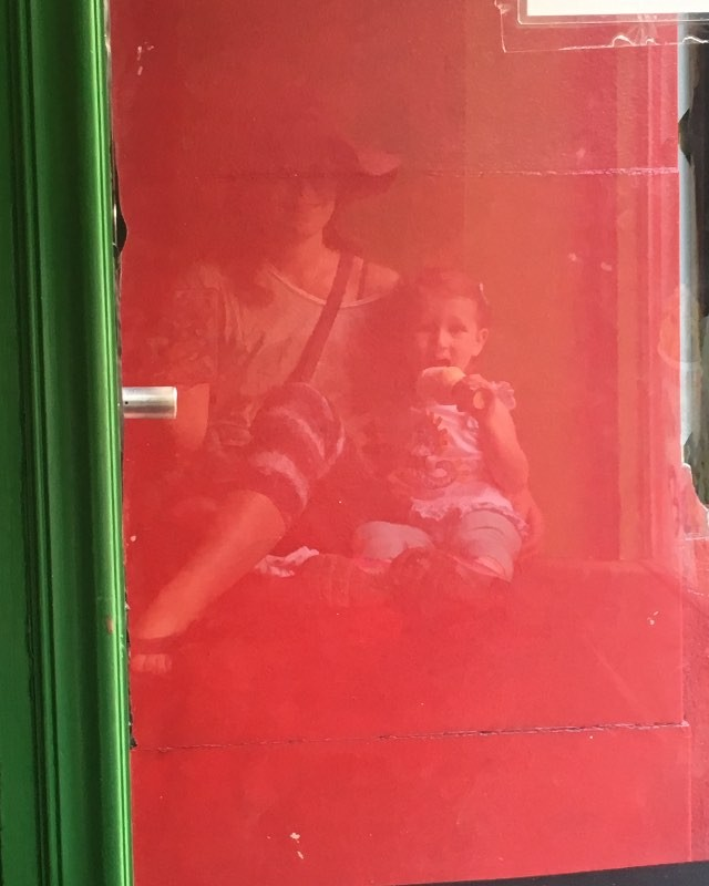 Ice cream store window - mother daughter sharing a cone.