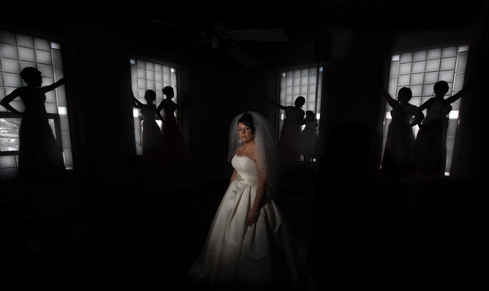 Caitlyn (Morris) Meitner poses prior to her wedding as her bridesmaids strike a pose, silhouetted against the windows of an old classroom.