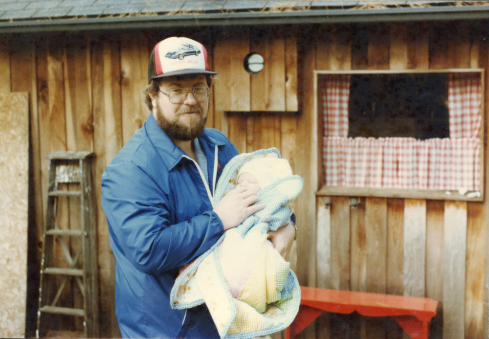 My dad holding me at our cottage when I was one month old.
