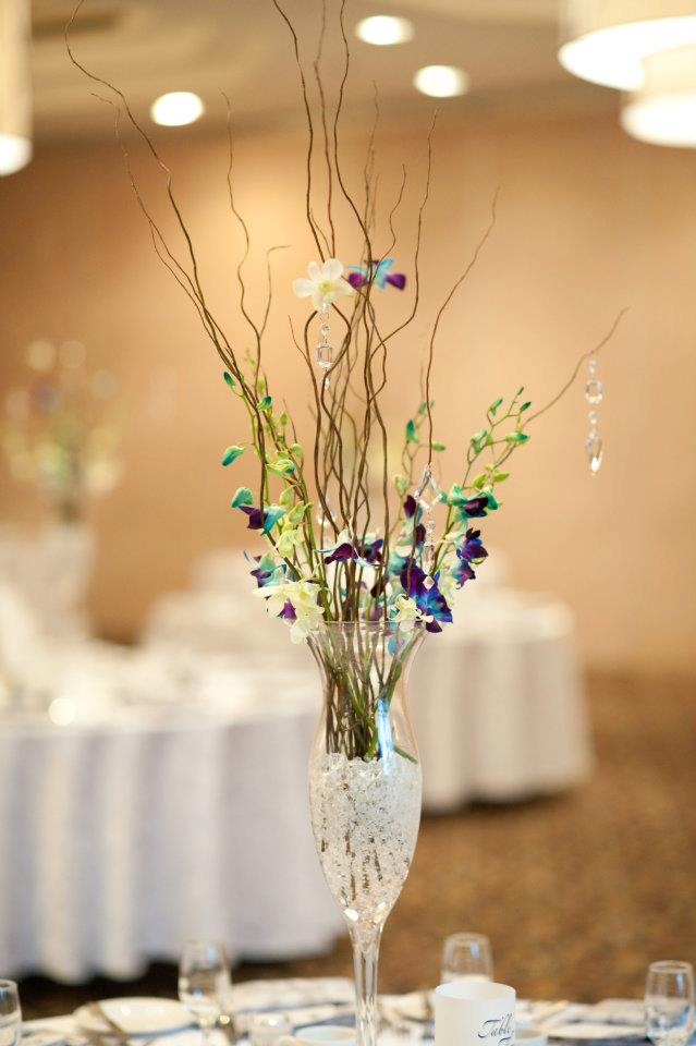 the centerpieces were trumpet vases filled with crystal gel, curly willow, filled with blue dendrobium orchids and beads hanging off the branches