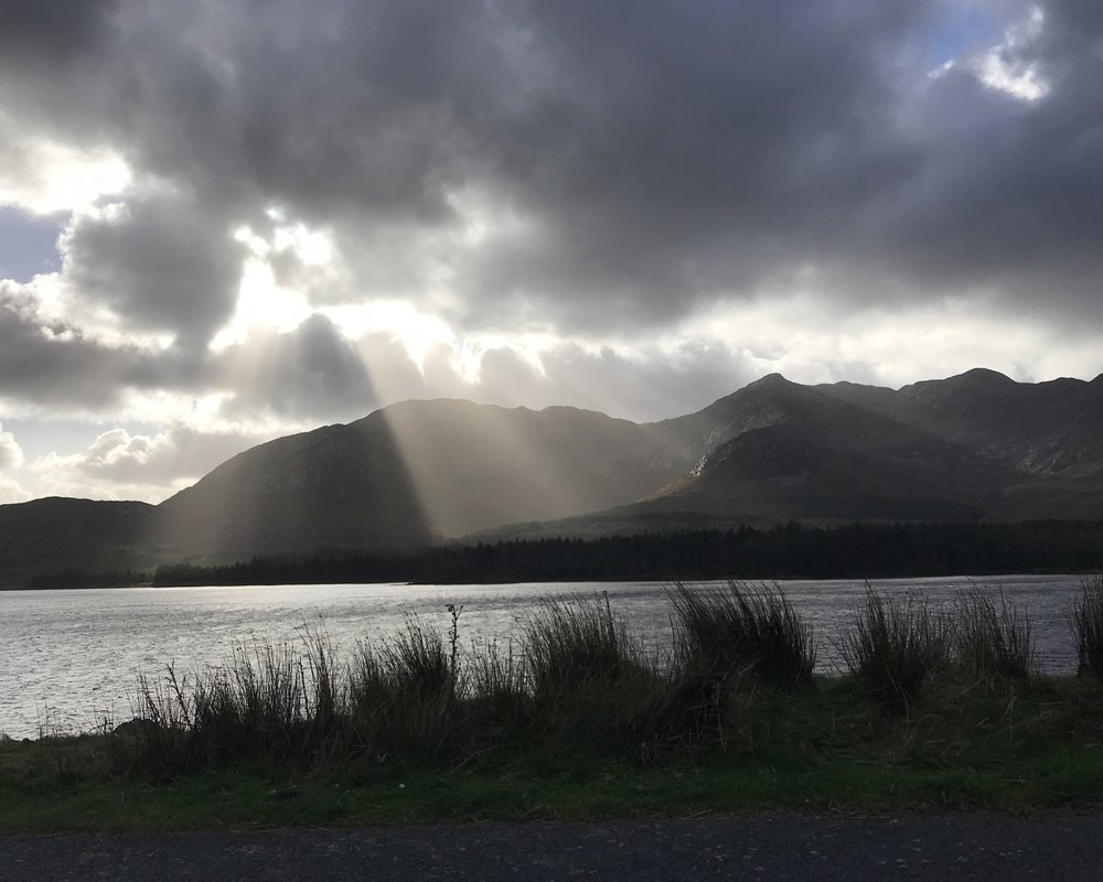 This is a photograph of Lough Inagh in County Galway, in Ireland. We were touring Connemara, and returning in the late afternoon to Galway, when this scene just appeared. I just shot it through the back window of the car we were passengers in. Pure luck to have caught the sun streaming down behind the clouds.. ©2017 Sean Walmsley;