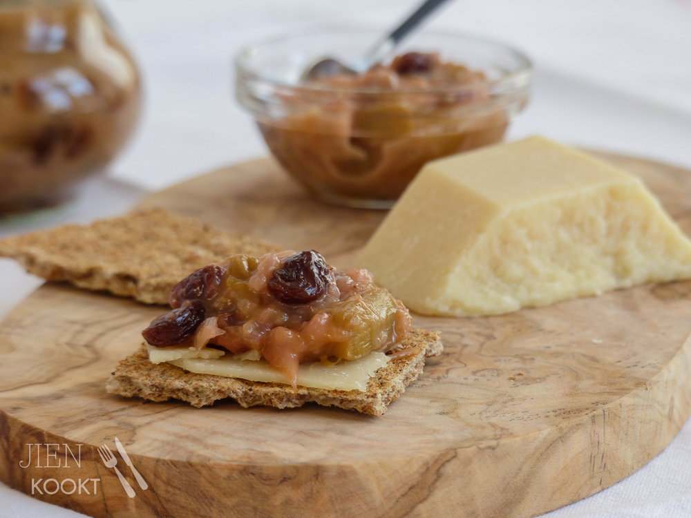 Rabarberchutney op een cracker met een dun plakje Parmezaanse kaas