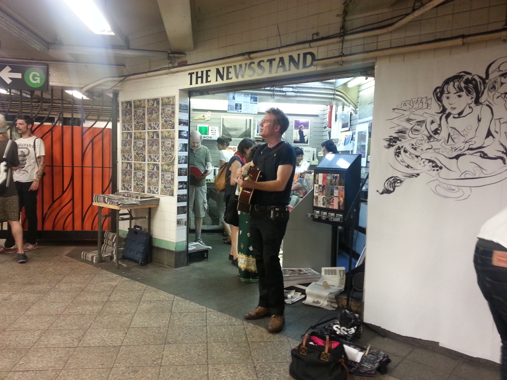 Marcellus Hall performing in front of The Newsstand