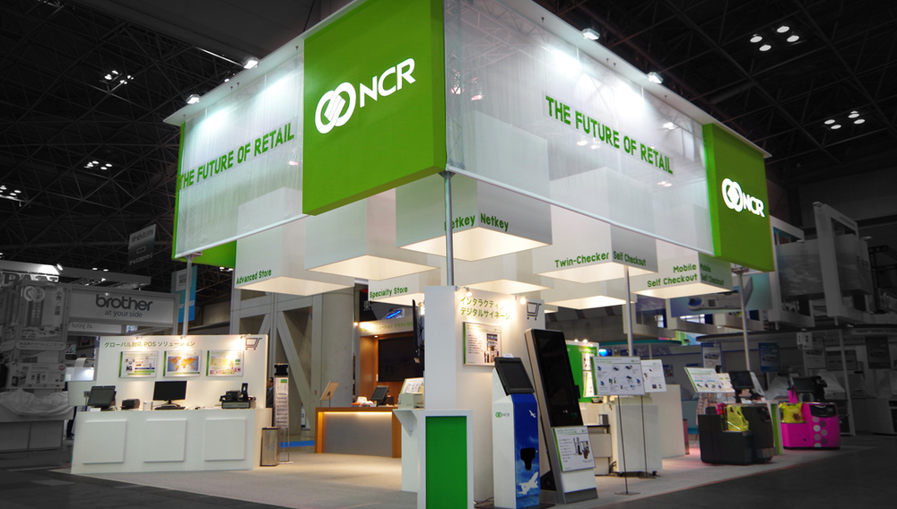 A trade show stand for NCR featuring the NCR Brand Block and NCR New Marker font.