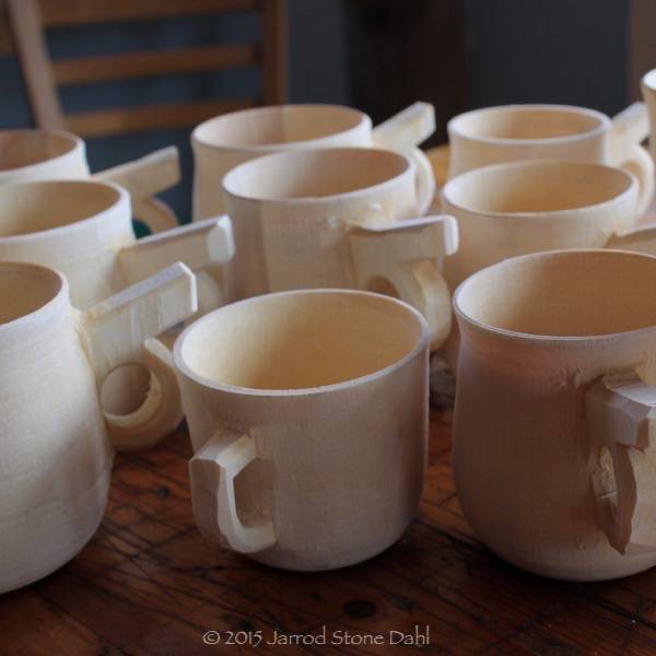 a batch or handled mugs ready for the oil/wax bath. These can only be turned on a pole lathe.
