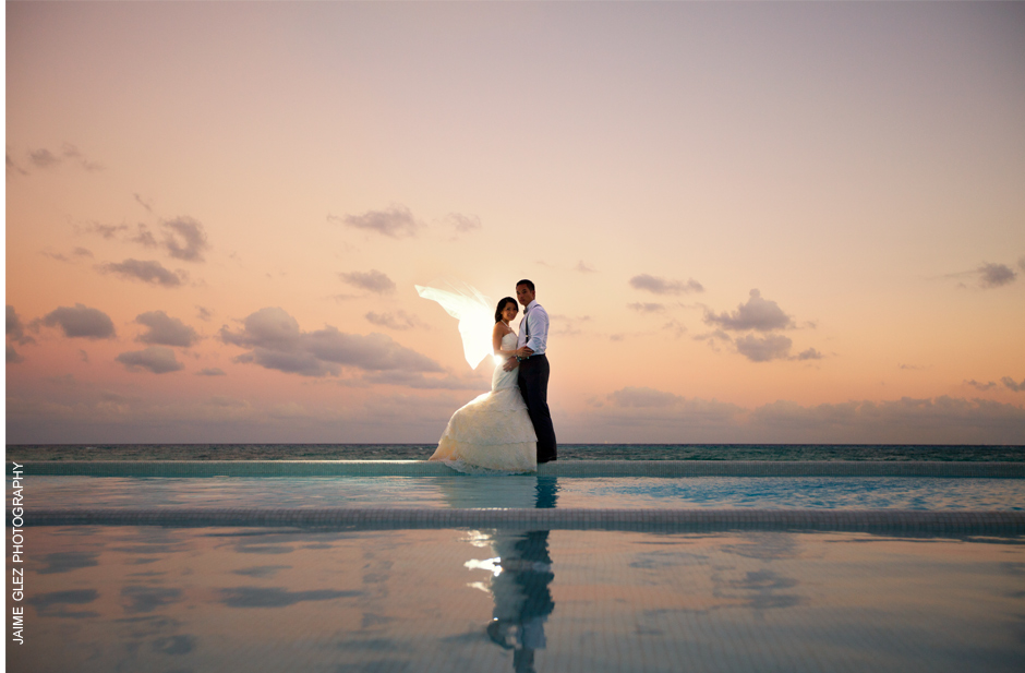 Beautiful couple in the glow of a caribbean sunset. Her veil flowed in the wind creating an angel wings against the setting sun. Unique moment!