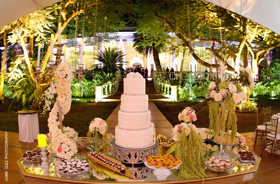 Love the way to present the wedding cake surrounded by flowers and petits fours!