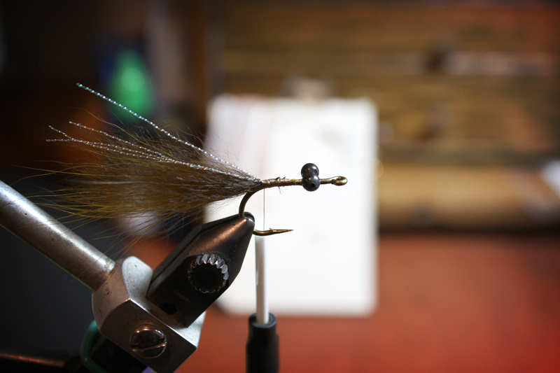tie in two strands of midge flash by the middle, fold the second half back and tie it down.