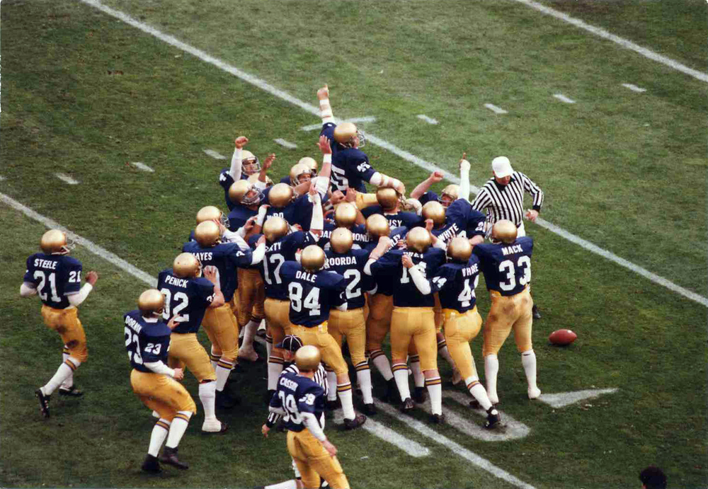 "Daniel ""Rudy"" Ruettiger being carried off the field."