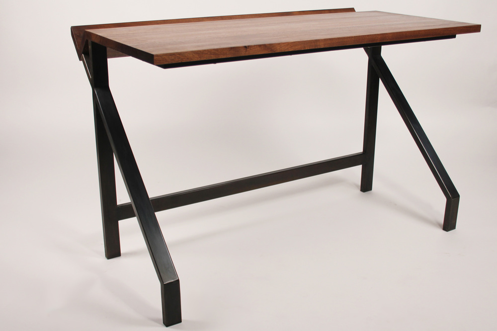 Solid walnut desk top with a  blackened steel frame, the nook at the back of the desk is designed to  keep the main surface of the desk clutter free. Books, papers, pens and  pretty much everything that could clutter your desk can be easily stored  in the back.