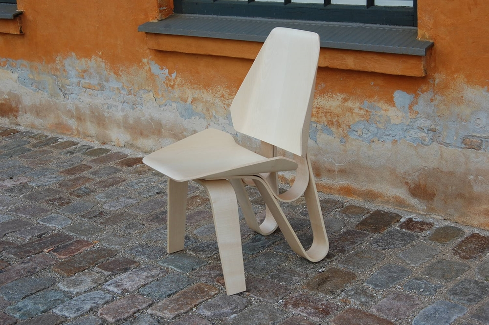 Designed and built in Copenhagen,  Denmark, it is made    entirely from maple and ash veneer.    The double loop system that makes up the back legs allows the backrest  to flex and it can be easily disassembled.    Click  HERE  to see process photos.