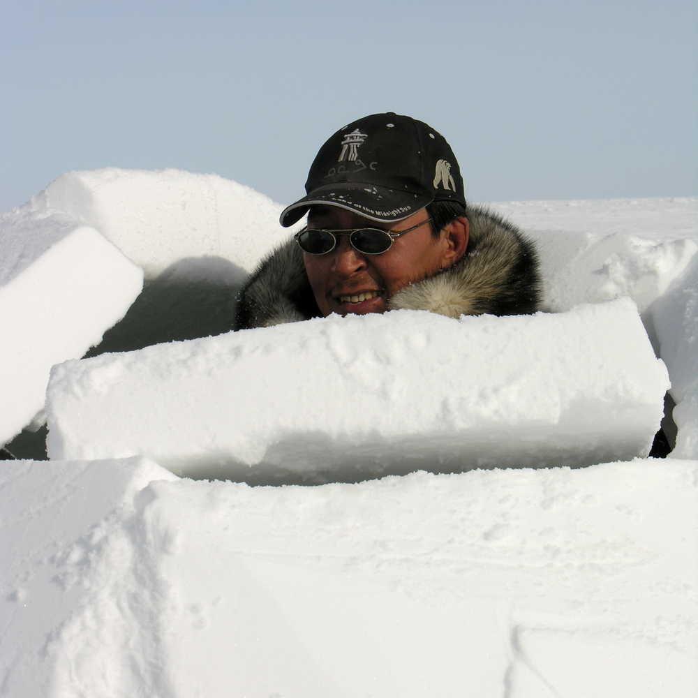 Inuit guide Joseph Kidlapik demonstrates building an igloo on frozen Hudson Bay, but you can make one in your own backyard! Photo by Katharine Fletcher.